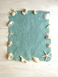 白い貝がらと水色の紙の写真素材 [FYI01170936]