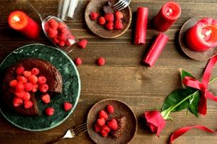 ラズベリーチョコレートケーキと赤い薔薇とキャンドル 黒木材背景の写真素材 [FYI01170980]