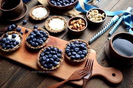 ブルーベリータルトとナッツ 黒木材背景の写真素材 [FYI01170992]