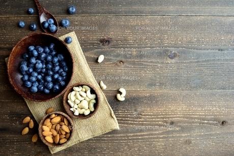 木製ボウルに盛ったブルーベリーとナッツ 黒木材背景の写真素材 [FYI01171000]