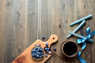 ブルーベリータルトとブルーのキャンドルとティーカップの写真素材 [FYI01171261]