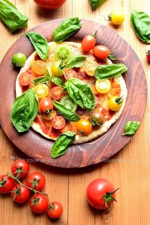 カラフルなトマトとバジルリーフのピザの写真素材 [FYI01171349]