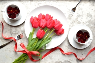 赤いチューリップの花束とペアの白い食器 白木材背景の写真素材 [FYI01172921]