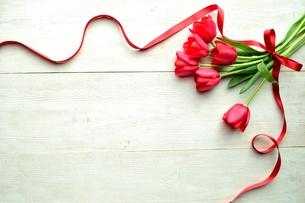 赤いリボンを結んだ赤いチューリップの花束 の写真素材 [FYI01172947]
