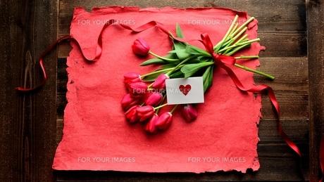 赤色のチューリップの花束とメッセージカードと赤い紙  の写真素材 [FYI01173294]