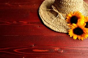 麦わら帽子と向日葵 茶色木材背景の写真素材 [FYI01173374]