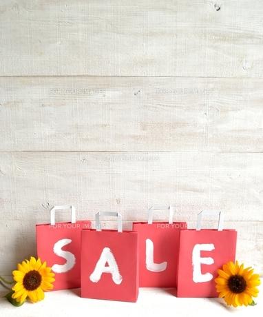 向日葵と赤いセール用紙袋の写真素材 [FYI01173381]
