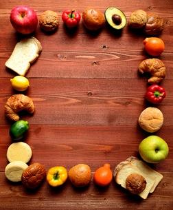 いろいろなパンとフルーツ 茶色木材背景の写真素材 [FYI01173544]