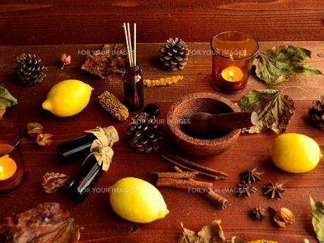 エッセンシャルオイルボトルとレモンと落葉 茶色木材背景の写真素材 [FYI01173594]