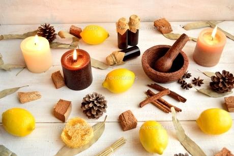 エッセンシャルオイルボトルとレモンとキャンドル 白木材背景の写真素材 [FYI01173611]