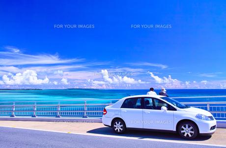 真夏の宮古島、伊良部大橋の駐車スペースから海を眺める観光客の写真素材 [FYI01173805]