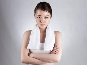 首からタオルをかけて腕組みをする女性の写真素材 [FYI01173978]