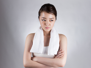 首からタオルをかけて腕組みをする女性の写真素材 [FYI01173979]