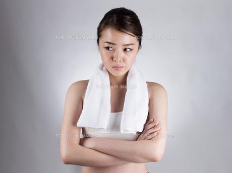 首からタオルをかけて腕組みをする女性の写真素材 [FYI01173980]