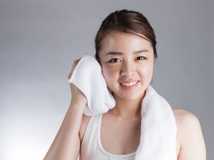 タオルで汗を拭く若い女性の写真素材 [FYI01173992]