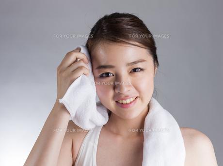 タオルで汗を拭く若い女性の写真素材 [FYI01173993]