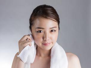 タオルで汗を拭く若い女性の写真素材 [FYI01173995]