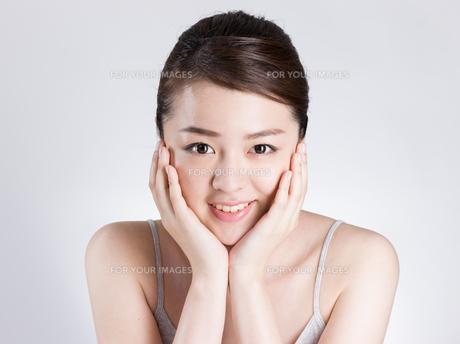 頰に手を添える女性の写真素材 [FYI01174085]