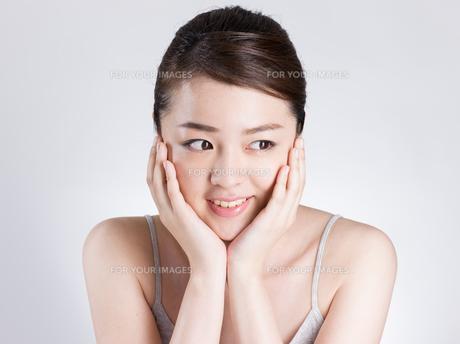頰に手を添える女性の写真素材 [FYI01174087]
