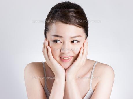 頰に手を添える女性の写真素材 [FYI01174089]