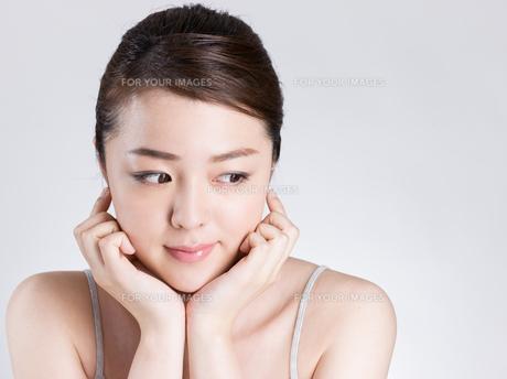 頰に手を添える女性の写真素材 [FYI01174091]