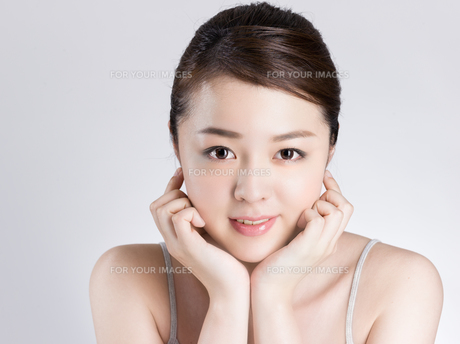 頰に手を添える女性の写真素材 [FYI01174092]