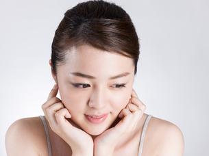 頰に手を添える女性の写真素材 [FYI01174093]