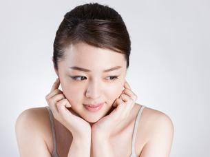 頰に手を添える女性の写真素材 [FYI01174094]