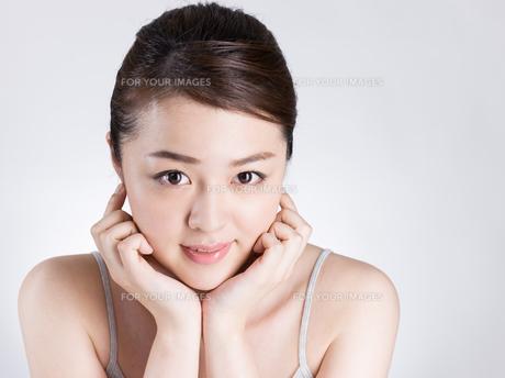 頰に手を添える女性の写真素材 [FYI01174095]