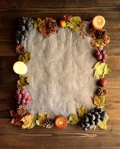 葡萄と落葉とキャンドル フレーム グレーの紙背景の写真素材 [FYI01174335]