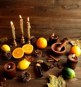柑橘系フルーツとエッセンシャルオイルボトルと落葉 黒木材背景の写真素材 [FYI01174432]