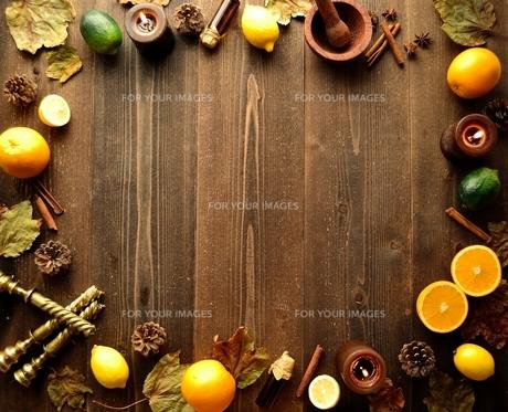 柑橘系フルーツとエッセンシャルオイルボトルと落葉フレーム 黒木材背景の写真素材 [FYI01174439]
