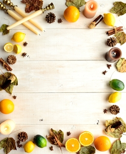 柑橘系フルーツとエッセンシャルオイルボトルと落葉 フレーム 白木材背景の写真素材 [FYI01174446]