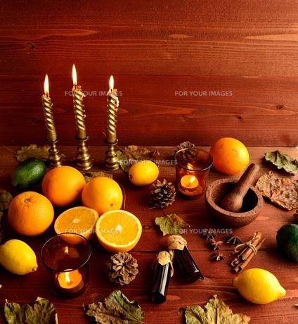 柑橘系フルーツとエッセンシャルオイルボトルと落葉 茶色木材背景の写真素材 [FYI01174448]