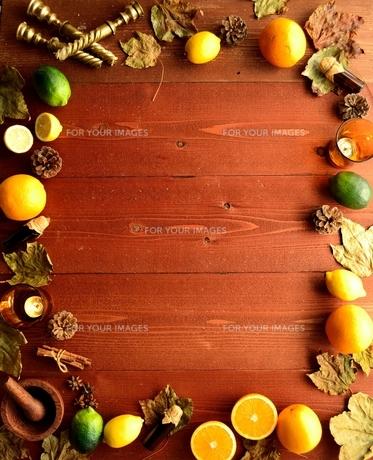 柑橘系フルーツとエッセンシャルオイルボトルと落葉 フレーム 茶色木材背景の写真素材 [FYI01174454]
