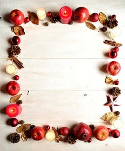 林檎とクリスマスオーナメントとシナモンスティック フレーム 白木材背景の写真素材 [FYI01175016]
