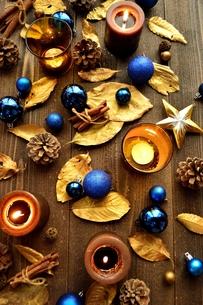 青いクリスマスオーナメントとキャンドルと金色の落葉 の写真素材 [FYI01175025]