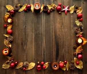 赤いクリスマスオーナメントとキャンドルと金色の落葉 フレームの写真素材 [FYI01175034]