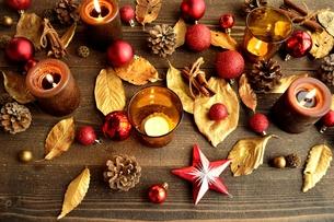 赤いクリスマスオーナメントとキャンドルと金色の落葉 の写真素材 [FYI01175039]