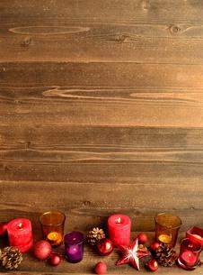 赤いクリスマスオーナメントとキャンドルとまつぼっくりの写真素材 [FYI01175099]