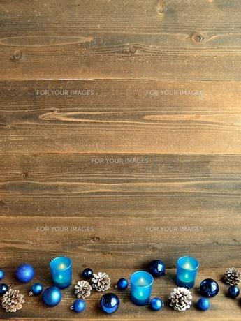 青いクリスマスオーナメントとキャンドルとまつぼっくりの写真素材 [FYI01175100]