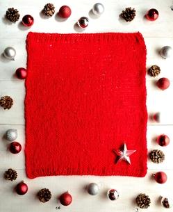 星型のクリスマスオーナメント 赤いニット背景の写真素材 [FYI01175568]