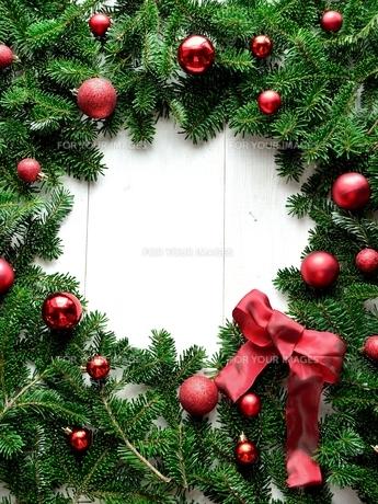赤いリボンとクリスマスオーナメントとモミの葉のフレームの写真素材 [FYI01176006]