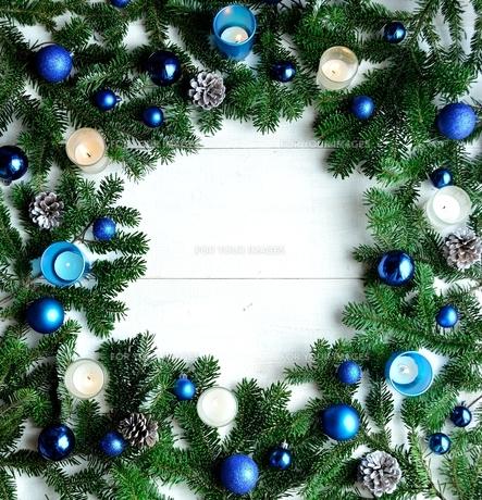 クリスマスオーナメントとキャンドルとモミの葉 フレーム ブルー系の写真素材 [FYI01176180]