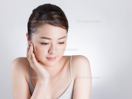 頰に手を添える女性の写真素材 [FYI01176386]