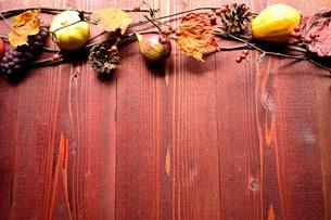 かぼちゃと果物の枯葉 茶色木材背景の写真素材 [FYI01176637]
