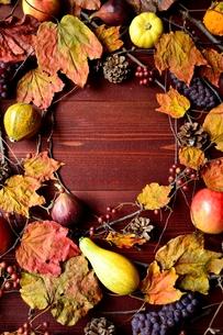 かぼちゃと果物の枯葉のフレーム 茶色木材背景の写真素材 [FYI01176680]