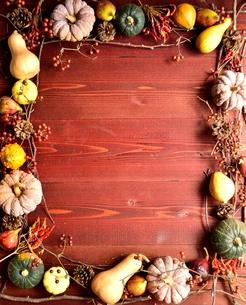 かぼちゃと枯葉のフレーム 茶色木材背景の写真素材 [FYI01176681]