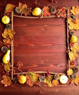 かぼちゃと枯葉のフレーム 茶色木材背景の写真素材 [FYI01176689]