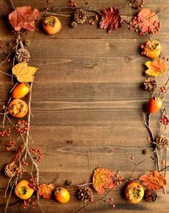 柿と枯葉のフレーム 木材背景の写真素材 [FYI01176718]